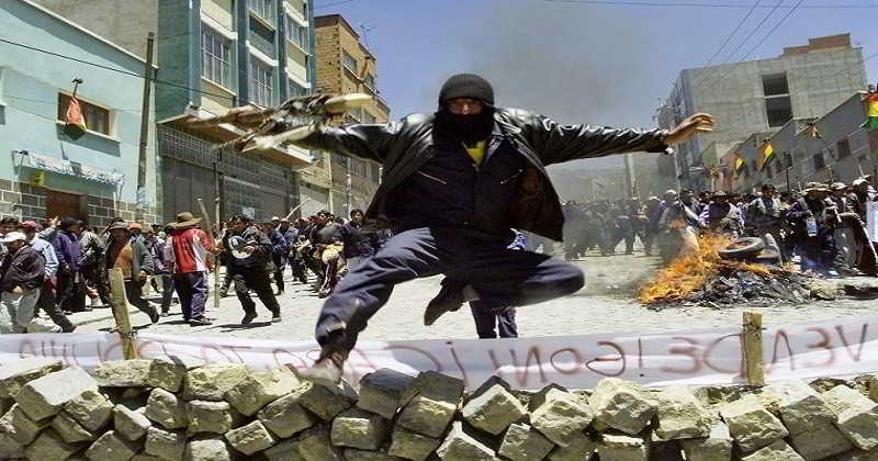 PICTURES OF THE YEAR 2003 - A Bolivian demonstrator holding a stick jumps over a barricade in a popular area of La Paz, October 13, 2003. Protests by the country's poor Indian majority against Sanchez de Lozada have spiraled in the last month amid an economic downturn in the nation of 8 million, one of the poorest in the Western Hemisphere. REUTERS/Jose Luis Quintana